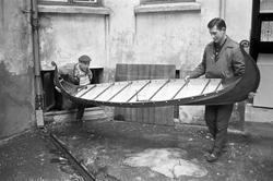"""Serie. To menn bærer ut en modell av vikingeskipet """"Osebergs"""
