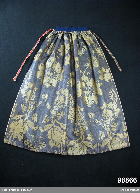 Förkläde av stormönstrad ylledamast i 1700-talsmönstring. Gulgrönt stort blommönster på mörkgrön botten. Förklädet är hopsytt av 2 hela vådbredder med stadkanter i var sida. Upptill rynkat mot en remsa av mörkblå vadmal med fastsydda knytband av olika hemvävda band. I ena sidan ett ripsband i brunt, blått och gult ullgarn på linvarp och i den andra sidan ett mönstervävt band med rött upplockat mönster på oblekt linnebotten. I mönstret är invävt initialerna L K O D. I nederkanten är förklädet skott med 3,5 cm brett ylleband skarvat av ett helrött band och ett rött med smala vita ränder. På insidan av midjelinningen broderat med vitt: 90. Förklädet är unikt och mycket välbevarat sånär som på några malhål på midjeremsan av vadmal. Ylledamast av denna höga kvalitet vävdes i första hand i Norwich, England, men tillverkning fanns även på andra platser eftersom detta var ett modernt tyg under 1700-talet. Till Sverige kom utländska tyger av denna sort in i allmogedräkten i slutet av 1700-talet och eftersom det var dyrbara köpetyger användes de till högtidsdräkt i första hand bröllopsdräkterna för både kvinnor och män, vanligast som livstycken och västar, i enstaka fall som kjolar och ännu mer sällan som förkläden.  I detta fall kan man se hur rapporten har sett ut, vilket är svårare på de tillskurna livstyckena. Eftersom sådana utländska tyger hade importförbud under 1700-talet kan de ha kommit illegalt via gränshandeln med Norge. Förklädet kom in tillsammans med ett par sammanbundna kjolväskor av  rött tyg med påsydda silverband, inv.nr  98867 som använts som brudklädsel. Det kan mycket väl vara från samma brud. /Berit Eldvik 2008-06-09