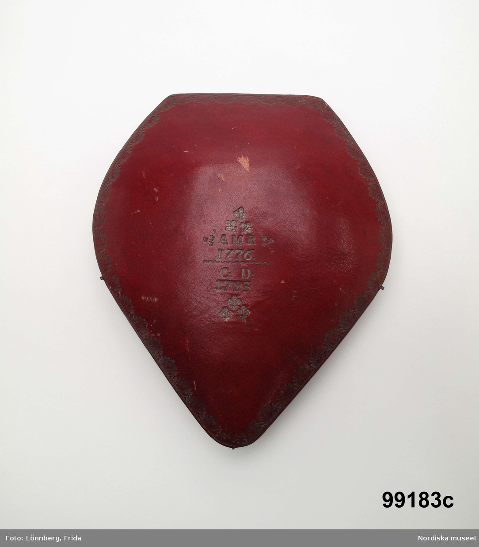 """Huvudliggaren: """"Brudkrona och krans i rött saffiansfodral med guldtryckt ornering. Kronan och kransen av konstgjort myrten. Märkt [etuiet] 'A.M.R. 1776' och 'C.D. 1783'. anv. 1775 [sic!] och 1783. Gåva 24/5 1904 gm testam. av Grevesmühl, Em. fru."""" a) Krona. b) krans c) etui.  Myrten."""