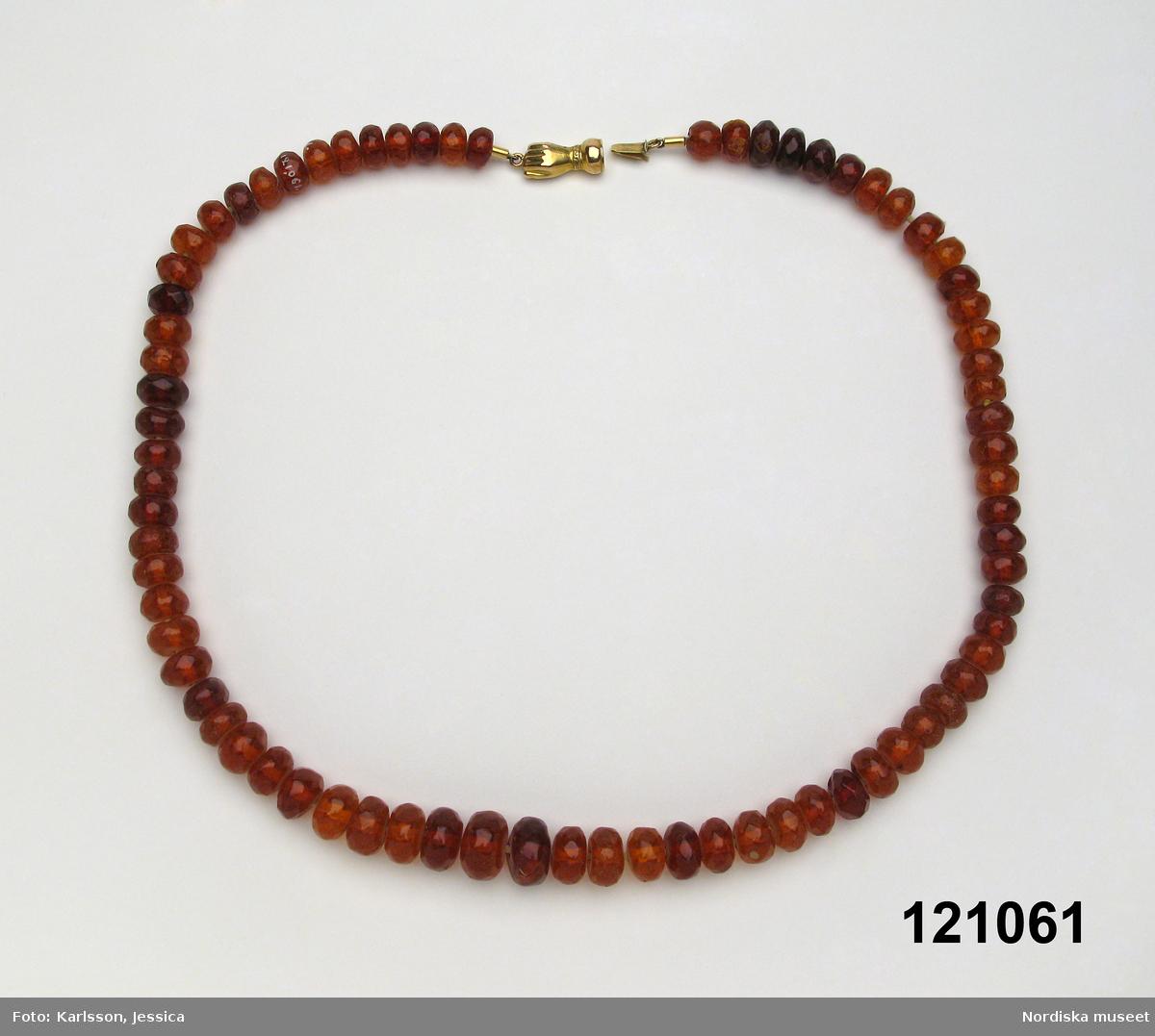 Materialet är bärnsten, metall och syntetisk tråd enligt konservator Thea Winther 2010.