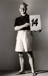 Nordiska Kompaniets kabaré april 1943. Man iförd shorts, kortärmad sportskjorta, sandaler och mössa med tofs. Han håller upp en skylt med talet 14.