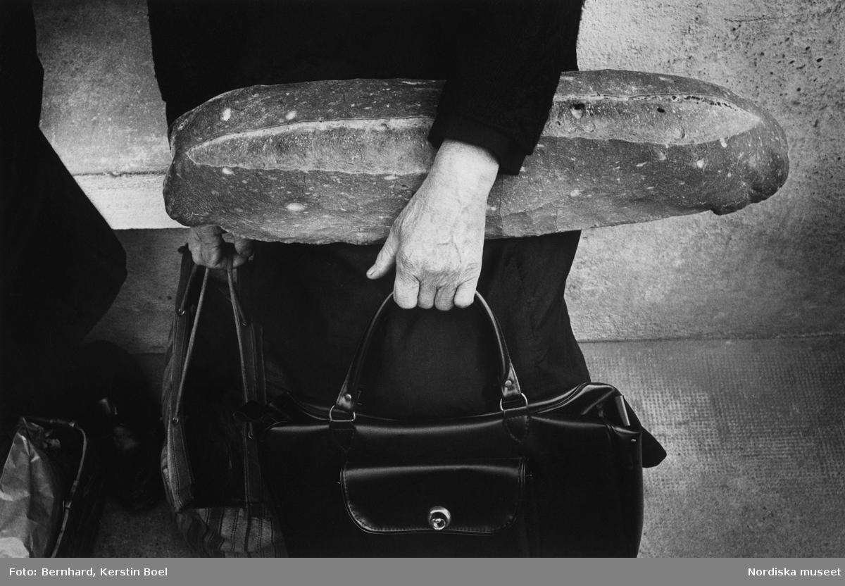 Kvinna som håller i två väskor och ett stort  bröd.
