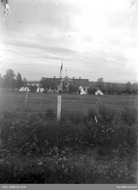 Vy över en landskap med bostadshus. Vita tält på gården framför huset.