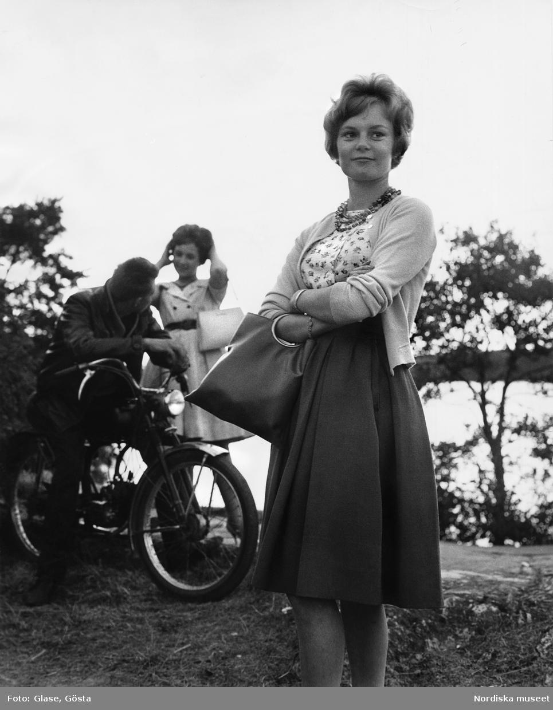 Handväska Och Handbagage : I f?rgrunden en ung kvinna med vid kjol blommig blus och