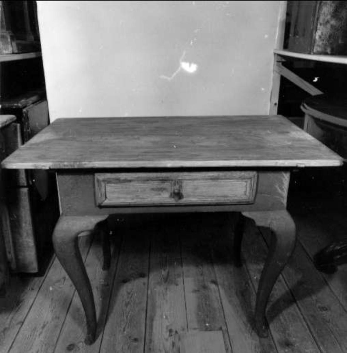 Rektangulärt bord med svängda ben. En låda i sargen. Hopfogat med dymlingar. Rester av röd färg och under denna vit och blå färg.