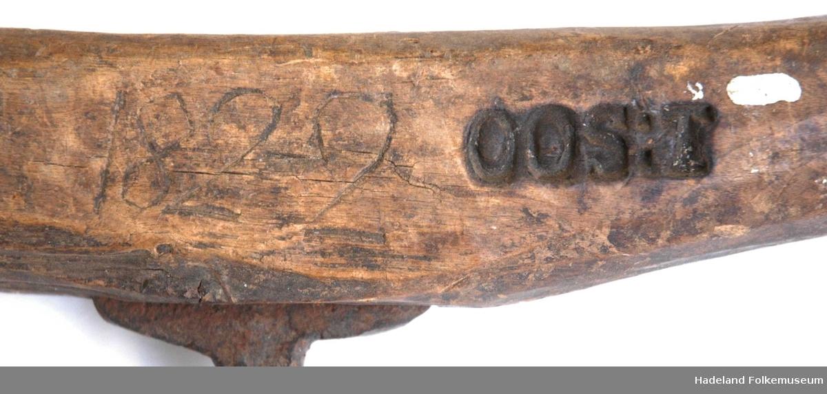 Bor av smidd jern, med tverrstilt håndtak av tre i motsatte ende.