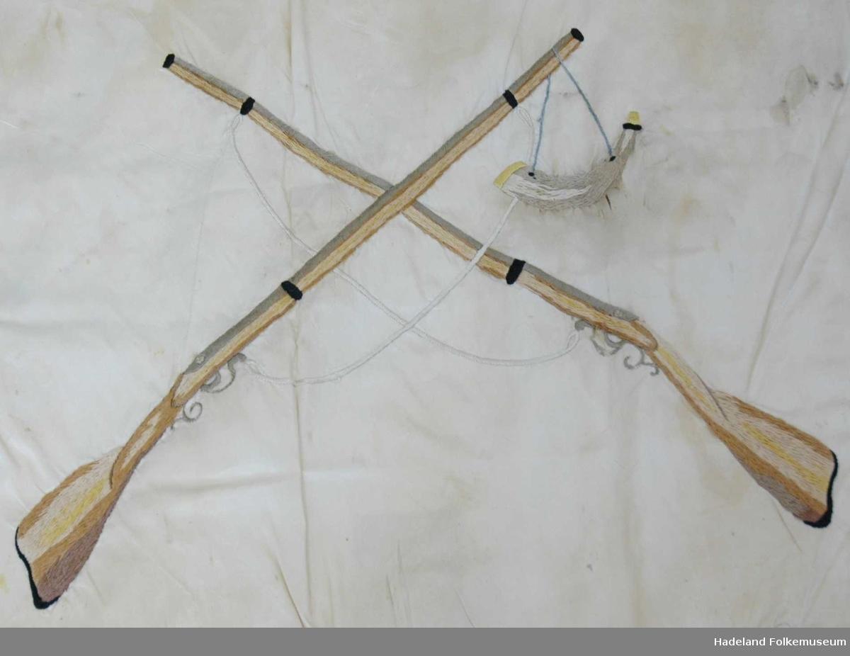 Fane av hvit silke. Løpegang på den ene siden har revnet. Brodert tekst, samt eikebladskrans med sløyfe omkring to gevær med påhengende krutthorn.