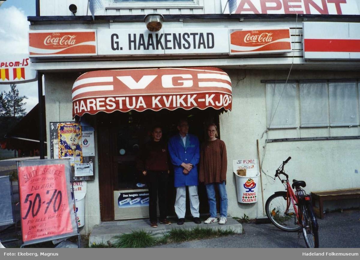 G. Haakenstad landhandel, senere Harestua kvikk-kjøp. Tre personer står utenfor ved inngangsdøra til matbutikken.