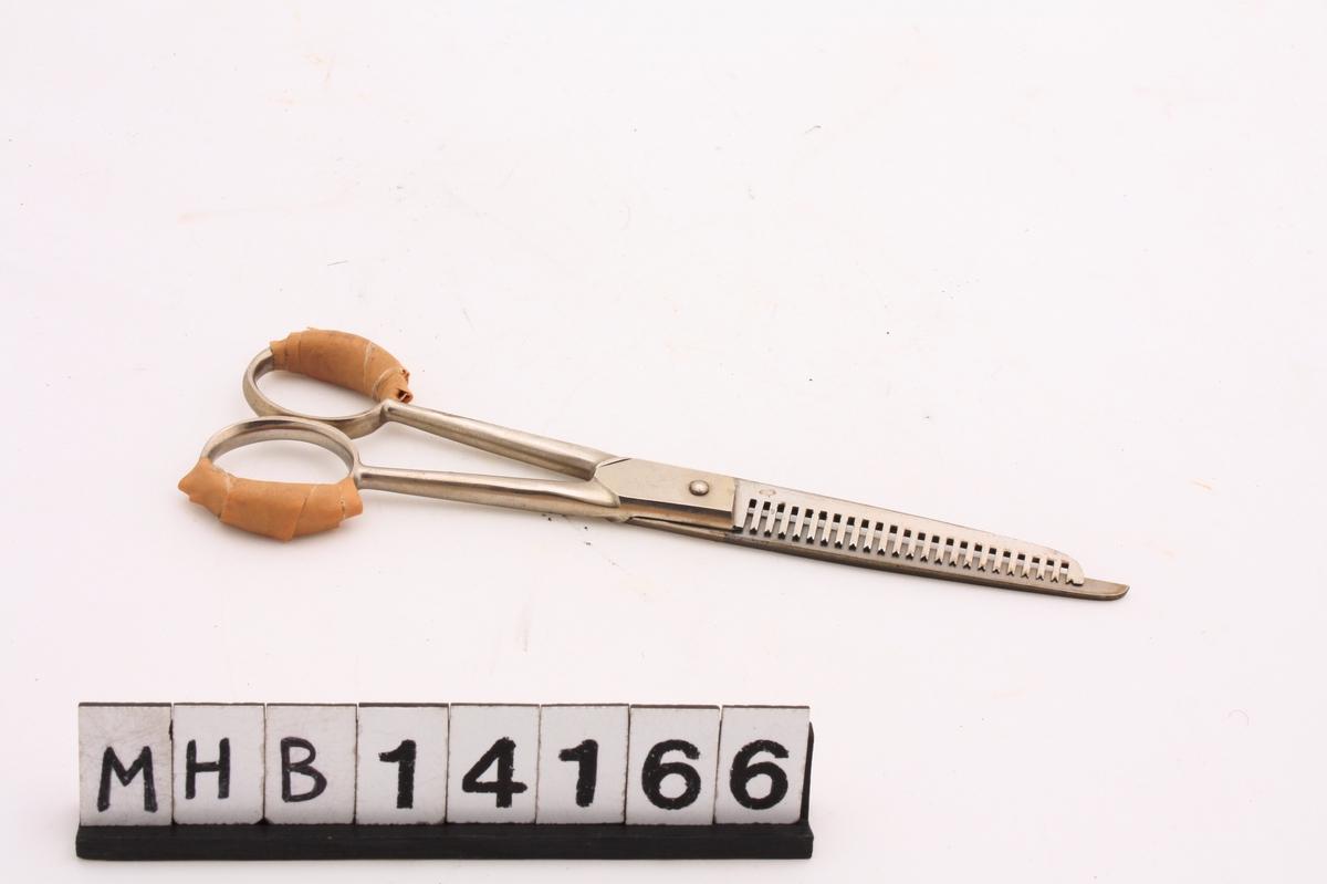 Frisørsaks i metall, til å tynne ut hår med. Det ene saksebladet er langt og skarpt, mens det andre er tagget. Håndtaket er todelt med ringer til å ha fingrene i. Begge ringene er delvis polstret med brun tape.
