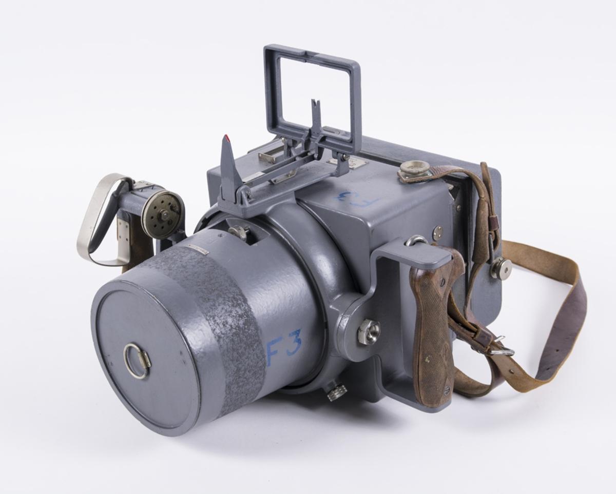 Handkamera HK 6 av märket Aga-Baltic. Brv 25,2 cm.  Handkamera av metall, grålackerad. Två handtag av trä. Försedd med rullfilmkassett m/38.