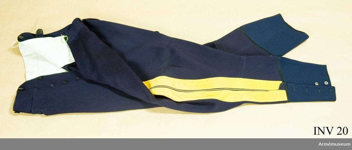 Mörkblå klädesdiagonal med dubbla klädeslister och emellan dem en gul passpoal. 6 knappar av svart bakelit i gylfen.  Byxbenen slutar strax under vaden där de knäpps med resp. 5 knappar av pärlemor.  Har för ridbyxor s.k. vid tillskärning. Har tillhört Gustav VI Adolf (1882-1973).