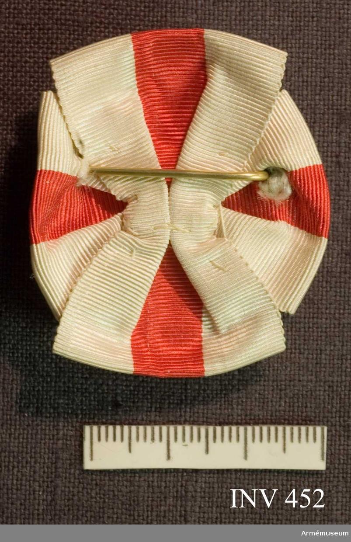 """Brosch av förgylld silver och blå emalj. Med drottning Sophias initialer """"D S F"""" krönt med en kunglig, sluten krona. Kronan är fylld med röd emalj.  Bokstävernas höjd: 14 mm. På ramen kartuscher.  På baksidan är broschnålen genomstucken ett band i rött och vitt ripsband som är förenad som en rosett och synlig från framsidan 7 mm.  På baksidan stansat """"G.Möllenborg Kongl.Hovjuvelerare Stockholm."""
