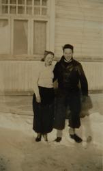 Ung kvinne og ung mann foran et hus