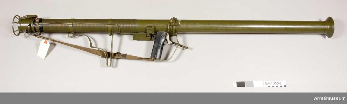 """Rocket Launcher AT MI. Bärrem av väv. Delbart eldrör, den främre delen 785 mm. Vapnet märkt """"M9AI (S6-A-1). Amerikansk bazooka (the Rocket Launcher, anti tank) som konstruerades 1942, hade ursprungligen 60 mm kaliber som senare ökades till 80 resp 90 mm. Eldröret är vik- och delbart. Tändningen av drivsatsen sker genom elektricitet. Gnistorna alstrades först genom ett par i handgreppet anbringade torrbatterier. Senare genom en liten handgenerator, efter tyskt mönster."""