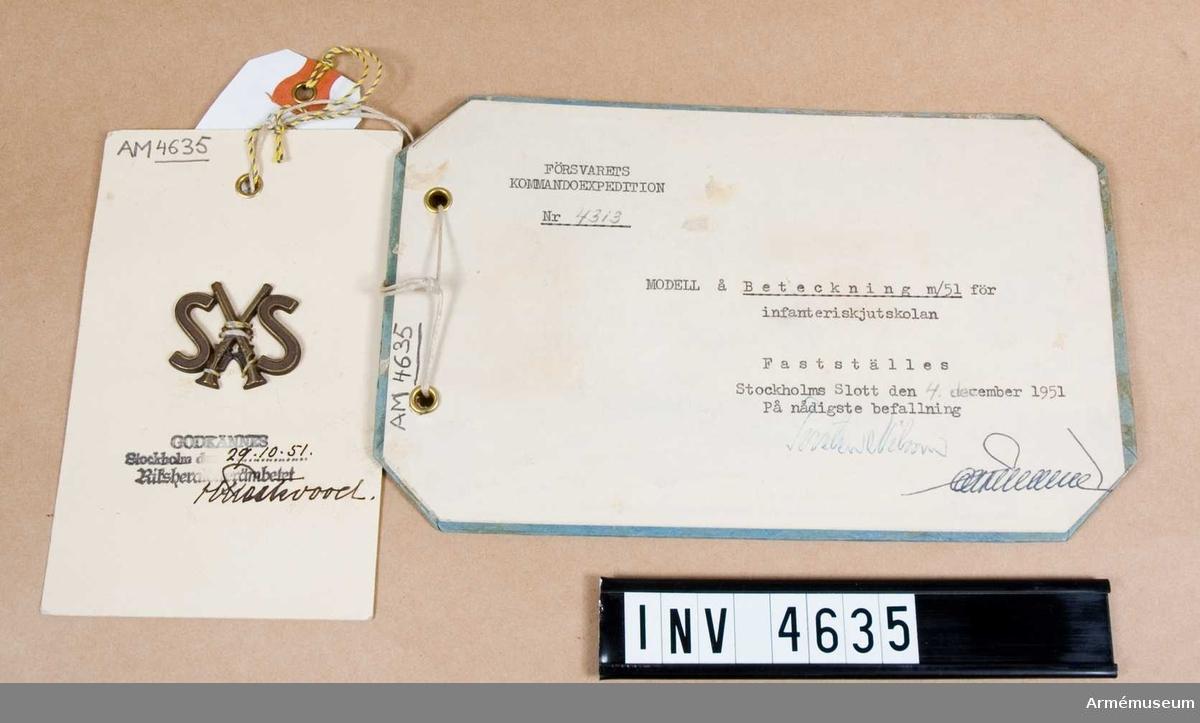 """Av bronsfärgad metall. Utgöres av två korslagda gevär mellan två stora """"S"""". Syddes fast på plagget. Anlades av off/uoff/ubef tjänstgörande vid skolan minst sex månader i följd samt av övningstrupp, vilken skolan förfogade över åren 1922-61.  Anbringades på axelklaffar på vapenrock/kappa m/1939 samt vapenrock m/1952. Till den senare i mattförgyllt utförande."""