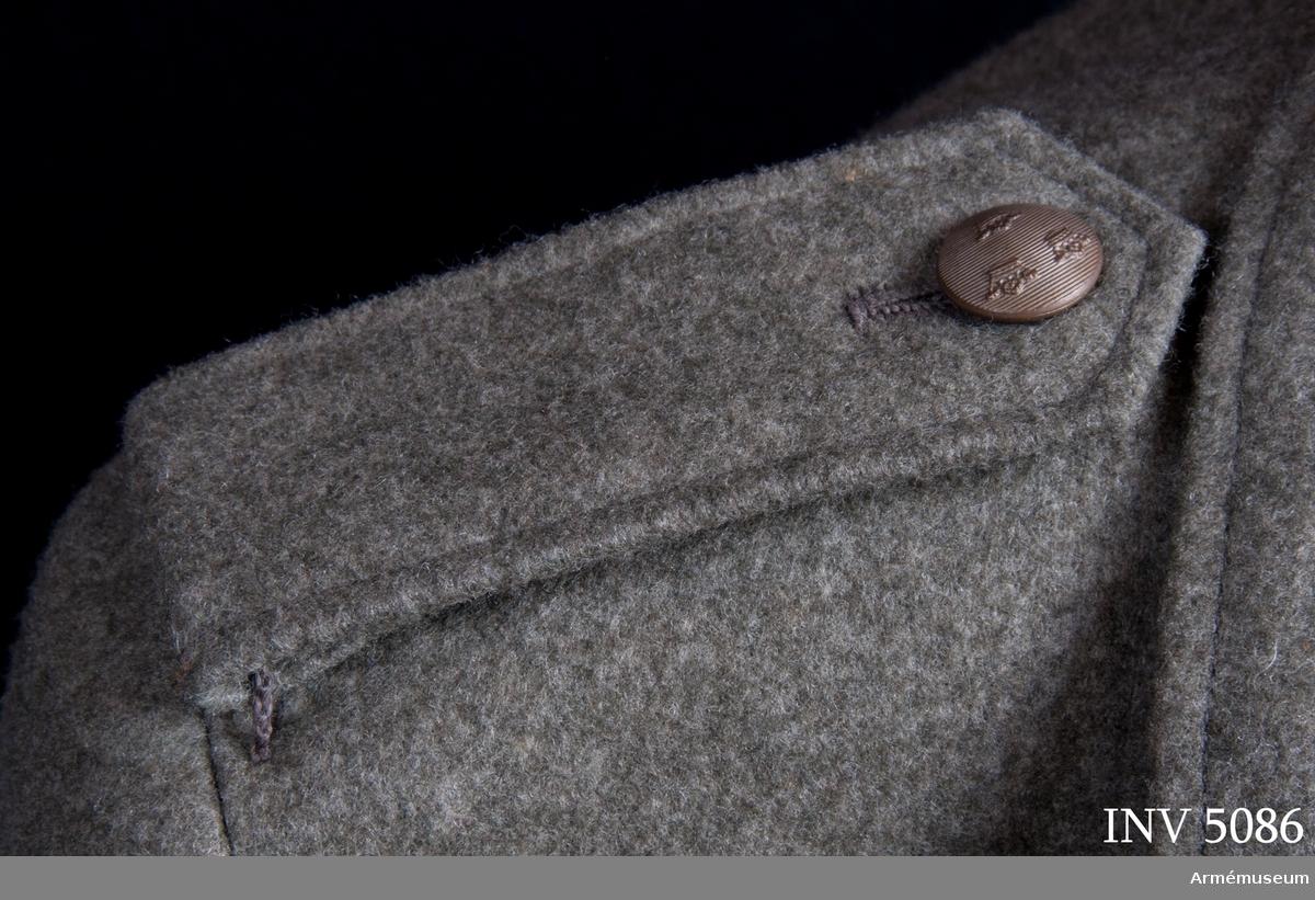 Axelklaff till kappa m/1942 kv. Kommiss. Fästes vid kappan med på denna sittande två trådsleifer. Knäpps med brunmatt knapp m/mindre av trekronorstyp.