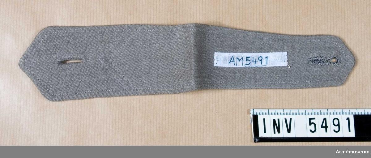 """Av grått ylletyg i kypert, något ruggat. Kan innehålla """"lump"""" eller cellull. Två knapphål f fastsättning på klänning.Det finns markering av två maskinsömmar där en vinkel har varit fastsydd.Gåva av E Lindberg, f Bokelund, Halmstad. Se AM 3635."""