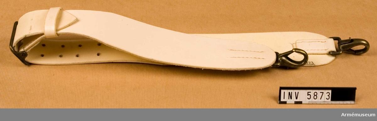 Samhörande nr är 5828-5899 + 6000-6099 + 6200-6205.Bärrem m/1954 till bastrumma.Gott skick X2. Färg: vit a.En kraftig bärrem, vit med gulmetallspänne med två torn och  rektangulärt. I vardera ändarna en karbinhake.