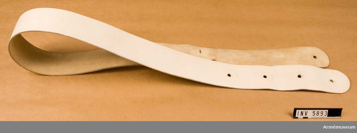 """Trumrem, vit, utan trumkrok och trumstockhållare.Gott skick X2. Längd 1575 mm, bredd 70 mm. Färg vit XA.Tillverkad av vitt läder med hål för kroken och hållaren.  Kroken fästes i trumman och remmen bärs över höger axel med  trumman vid vänster lår.Källa: Bo Ancker """"Vaktparaden kommer"""".Uni A 1977 6:502."""
