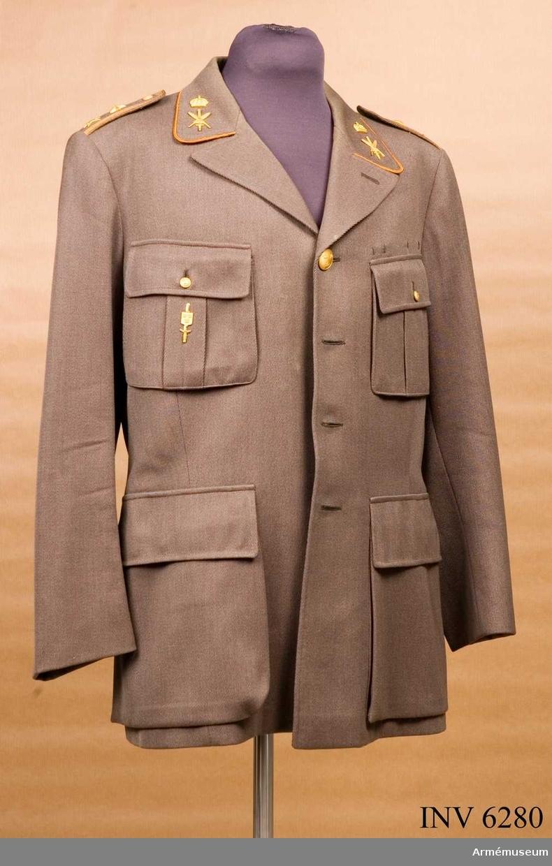 """Storlek E 100. Tillverkad i ett s k cellulltyg, en textilfiber ur cellulosa (numera rayon), i gängse snitt. Den har majors gradbeteckning och stabsredaktörsemblem på axelklaffar och kragsnibbar. Kragen är kantad med orange galon. Emblemen är mattförgyllda m/1952. På höger bröstficka  försvarsstabstecken. I vänster ficka skräddarens etikett: """"Hedlunds kläder tel 61 72 78 Artillerigatan 57 Stockholm den 17 Nov 1956 1538 Stabsred Westerlund"""". Uniformen kunde bäras vid: """"Övningar, pressbesök, kurser och andra tillfällen"""". Givaren, Karl-Erik Westerlund, F förste stabsredaktör, har  givit en historik över underformen, bil 19810522 nr 345."""