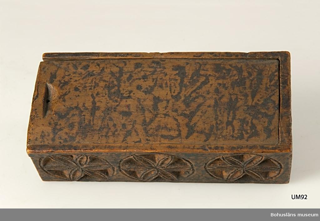 """Rektangulär låda med skjutlock upptill. Långsidorna har karvsnittsdekor bestående av rosetter. En av kortsidorna har årtalet """"1846"""" inskuret. Under botten är följande inskuret; """"J D 13 J ONS"""" samt ifyllt med blå färg. Målad med brun färg som antingen är marmorerad eller har """"krupit"""".  Litteratur. Gjaerder, Per, Esker og tiner, C. Huitfeldts förlag, Oslo, 1981, s. 48-50.  Se Knut Adrian Andersons """"Katalog I, A. yngre föremål"""" under Uddevalla museum/förening D 2A:1 i arkivet.  Ur handskrivna katalogen 1957-1958: """"Trälåda Bottenmått: 13 x 5,5 H. 4. Trä med skuren ornering. Föremålet helt. Svarteborg. Bohusl.""""  Lappkatalog: 84"""