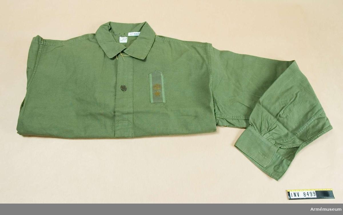 Samhörande med AM 8499.Skjorta m/1958, fält-.Tillverkad av olivgrönt bomullstyg med ruggad avigsida s k flanell, har sprund mitt fram, mjuk krage, nedvikt och enkel manschett på ärmen. På vänstra sidan av bröstet en gradbeteckning för major på grönt textilband. Sprund i sidorna nedtill. Användes med långbyxor m/1959, AM 8498.