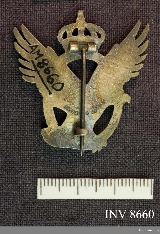 Av silver. En lyftande örn i ett ovalt märke krönt av kunglig krona. Frånsidan har silverstämplar.
