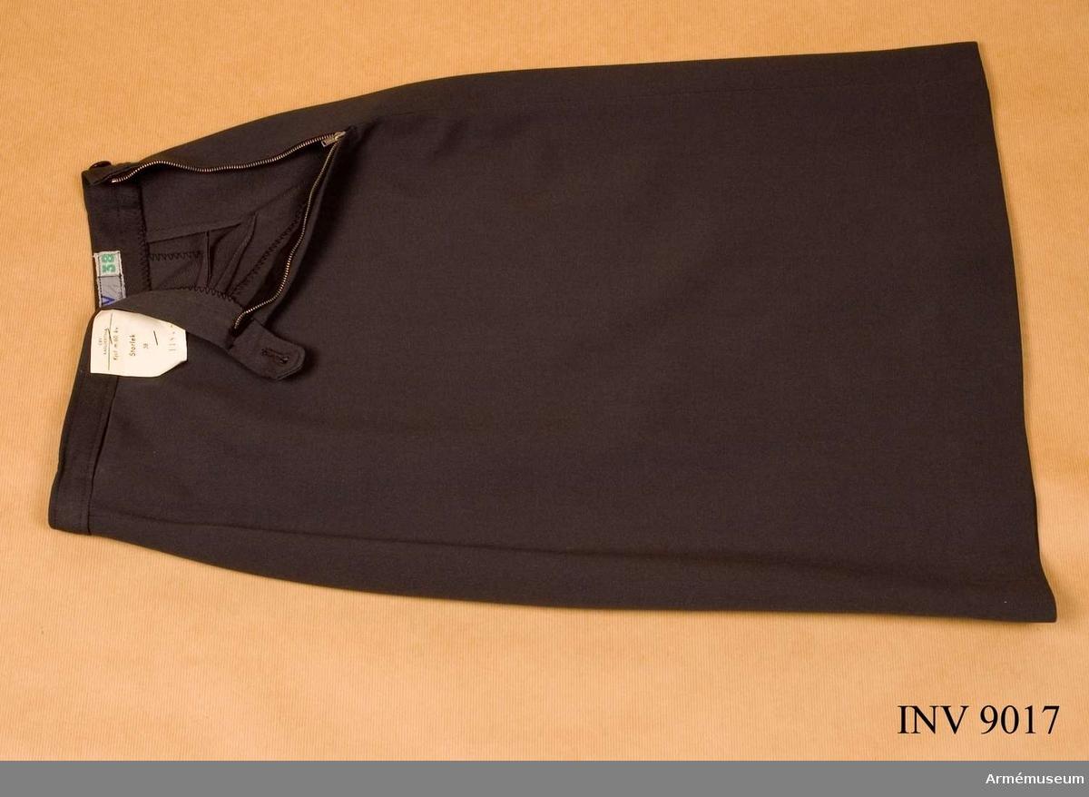 """Tillverkad i stålgrått tyg, har motveck på bakvåden samt blixtlås i vänstra sidan. Sydd med linning i midjan. Linningen är märkt """"CBV Karlskrona 38"""" (storleken).  Samhörande nr är AM.9017 - 9021"""