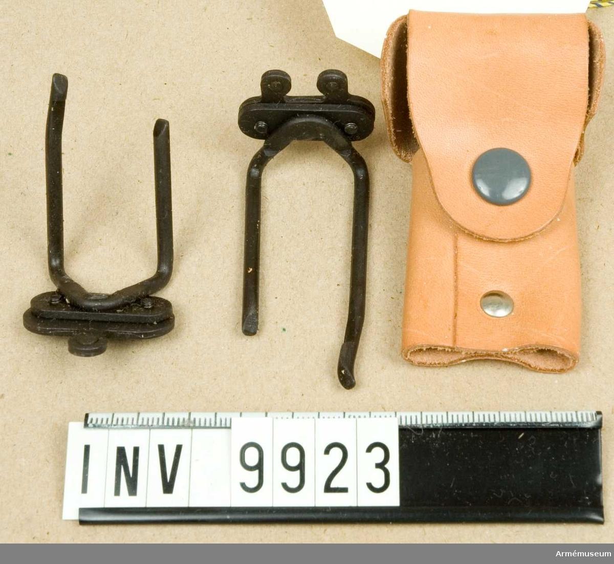 """Mörkerriktmedel.För kulsprutepistol m/1945, försökstyp 1, 3-punkt, 1954.Består av: 1 st fodral av läder märkt """"Kpist 1"""". 1 st korn märkt """"Kpist 1"""". 1 st sikte märkt """"Kpist 1"""".Konstruerad av KATF VaB 1. Truppförsök: 1953-55 jml Ao nr 60:26 den 29/9 1954. Principen fastställd jfr Ast/Utr nr 60:26 den 30/4 1955. Tillhör: PcU/H. Blysigill märkt: """"AKGF""""- en krona med två svärd i kors.Gåva från FMV/A:AIL försöksgrupp."""