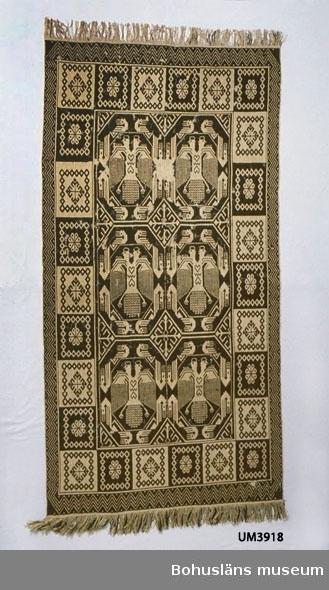 """Vävnad i mönstrad dubbelväv av mörkbrunt ullgarn och oblekt lingarn, båda hemspunna. Bonaden är en rekonstruktion. Har dubbla bårder, ytterst ett sicksackmönster och innanför det kvadrater med två olika mönsterfigurer (runduddig stjärna och rombformat motiv bildat av blommor?), i mittspegeln rader av dubbelörnar (två bredvid varandra på bredden). Fransar av varpen. Langettstygn sydda runt kanten för att tyget inte ska gå upp. På baksidan en fastsydd tygetikett med texten: Kopia Föremålets art o benämning: Bonad, """"Dubbelörnen"""" Teknik o Storlek: Finnvävnad 1,95 x 1 m Material: Lin o ull båda hemspunna. Tillverkare: Annie Johansson, Norra Bäck, Stenkyrka skn. Tjörns härad. Bohuslän. Ägare: Uddevalla museum Inköpt 1934.  På baksidan även påsydd linnelapp med siffran 2 och papperslapp med lackstämpel:""""UDDEVALLA M(oläsligt)"""" ska vara MUSEUM. Utställd vid Allmänna svenska distriktslantbruksmötet i Axvall 1935 i klass 262 B Avdelning X Grupp 15 Hemslöjd. Utställare: Göteborgs och Bohusläns Hemslöjdsförening, Askim. Har ytterligare en etikett av metall och papper fastklämd på baksidan, där står """"Dac 54"""" (gammalt katalognummer) och """"49954 215.-"""". Hål efter insektsangrepp över stora delar av bonaden, de flesta markerade med vit sytråd.  Ur handskrivna katalogen 1957-1958: Finskvävnad, """"Dubbelörn"""" L. c:a 1,95 m. Br.c:a 1 m. Svenskull o lin, brun o vit (hemspun.) Garnet i vävn. trasigt på ett flertal ställen. Stenkyrka, Bohuslän."""