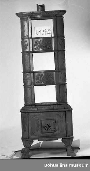 """Föremålet visas i basutställningen Gränsland, Bohusläns museum, Uddevalla.  Uppbyggd av ett flertal delar i gjutjärn, rikt dekorerade. Troligen tillverkad i Norge.  Ur handskrivna katalogen 1957-1958: Järnkamin H. 192 cm; uppbyggd av ett flertal delar i gjutjärn, rikt dekorerade; hel.  Lappkatalog:90: Kamin med kokplattor i tre våningar. Fötter i form av tassar, rikligt dekorerad med slingrande växtornament. L 680mm B 500 h 1820  Bilagepärm: Svartvit fotokopia på kaminen ihopsatt.  Litt:  Hamran, Ulf: Gamle ovner i Norge. 1989         Nygaåd-Nilssen, Arne: Norsk jernskulptur 1-2"""", 1944."""