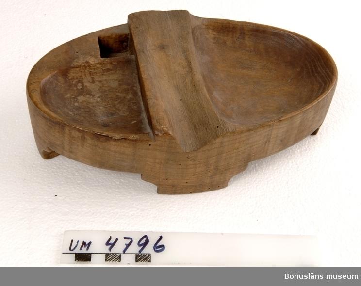 Tobaksbräde av trä. Ur handskrivna katalogen 1957-1958: Tobaksask L. 23: Br. 12,5 cm: H. 7,5 cm. Skuren i ask? Omålad, 4 fötter; i mitten en tvärgående upphöjn. att skära tobaken på? Maskhål.  Lappkatalog: 95  Ur Svenska Akademiens ordbok: TOBAKS-TALLRIK . (†) tallrik för rökverk o. d.  STRÅLE RörstrH 1: 49 ( i handl. fr. 1733) . 1 st. Tobakstalrick af Wallnöte träd med låck.  BoupptRasbo 1754 .  BoupptVäxjö 1784 . -