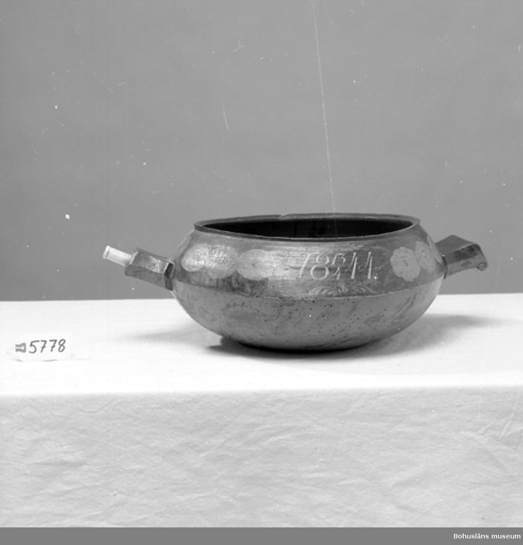 """571 Användningstid 1844-1954? 435 Motivkat DEKORATIVT  Svarvad skål, rund med handtag och pip. Den sistnämnda har en förlängning av skuret ben. Inventerat 1996-04-30 AN Neg.nr UMFF 446, Kerstin Lychous dia 531  Ur handskrivna katalogen 1957-1958: Pipskål 18 13/4 44 D. (upptill) c:a 35 cm, H. 18 cm; svarvad m. pip och handtag; i pipen en förlängn. av vitt ben; målad i rött, blått och ockragult m. dekor och inskr. i vitt rött och grönt; """"18 13/4 44"""", """"A Andersson"""". Maskäten.  Lappkatalog: 67"""