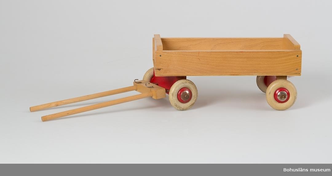 Rektangulär vagn, fyra gummihjul, varav främre paret ledat. Skaklar. Se UM015810