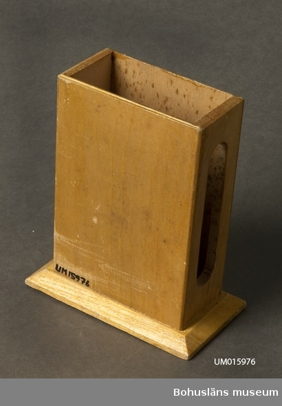 """För stor tändsticksask. I sidan öppning för plånet. Framsidan pryds med bild av Uddevallas kyrkas klocktorn, samt på sockeln namnet """"Uddevalla"""".  Se UM015810"""