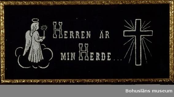 """Religiös tavla. Blått tryck med svart i vit färg och glitter.  I motivet texten: """"Herren är min Herde"""", omgivet av ljusbärande ängel och kors med strålkrans. Inramad med glas och guldfärgad gipsram."""