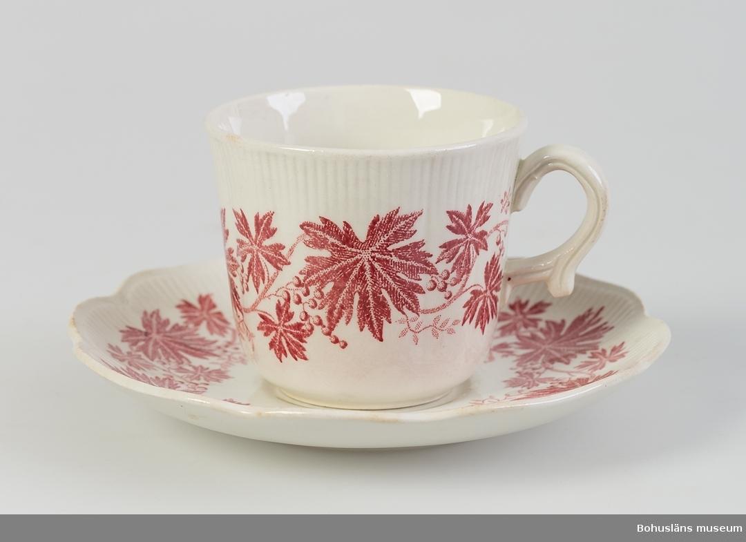 """Godronnerad kant på kopp och fat. Dekor av röda vinlöv, koppartryck. Ur servis """"Röd vinranka"""" Formgivare: Arthur Percy."""