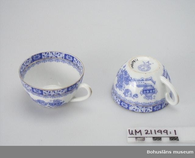 """594 Landskap BOHUSLÄN  Koppen stämplad i botten: """"Blau China Deutschland"""". Blå dekor på vit botten, guldränder. Överdelen är mönstrad på insidan. Fyra koppar är spruckna."""