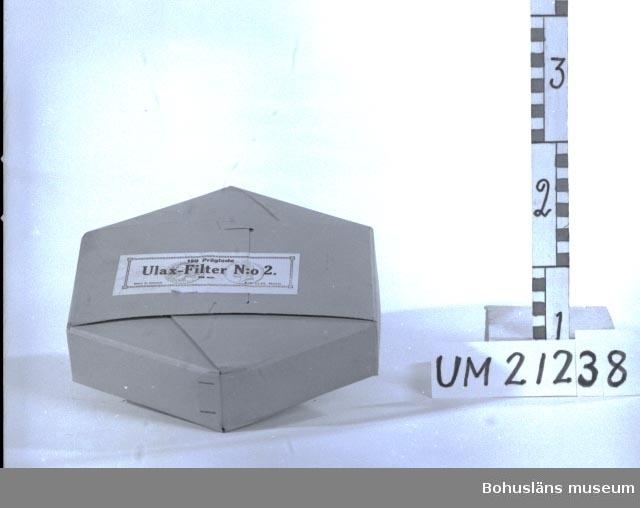 """412 Förvärvstillst OANVÄNT 594 Landskap BOHUSLÄN 394 Landskap ÖSTERGÖTLAND  Sexkantig låda av brun papp. Etikett med text: """"150 Präglade Ulax-Filter N:o 2. 235 mm. MADE IN SWEDEN A.-B. ULAX, Motala."""", samt lantbruksutställningsmedaljong från 1906.  Omkatalogiserat 1997-01-16 GH.  UMFF 5:4"""