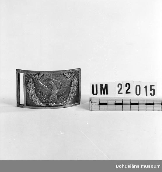 """410 Mått/Vikt ! TJ 1 CM 594 Landskap BOHUSLÄN  Bilden på spännet föreställer en lagerkrans i vit metall. Innuti denna örn med sköld på bröstet. I ena klon håller den en lagerkvist och i den andra tre pilar. I näbbet en banderoll med text: """"Pluribusunum"""", vilket betyder: """"Enhet genom mångfald"""".       UMFF 72:9"""