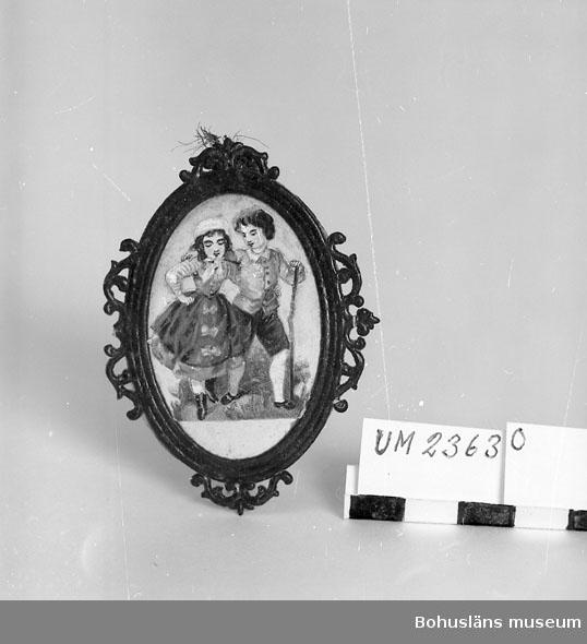 594 Landskap BOHUSLÄN  Oval form, brun ram med genombruten dekor. Påklistrad bild i flera färger.  Neg. nr UM 147:1