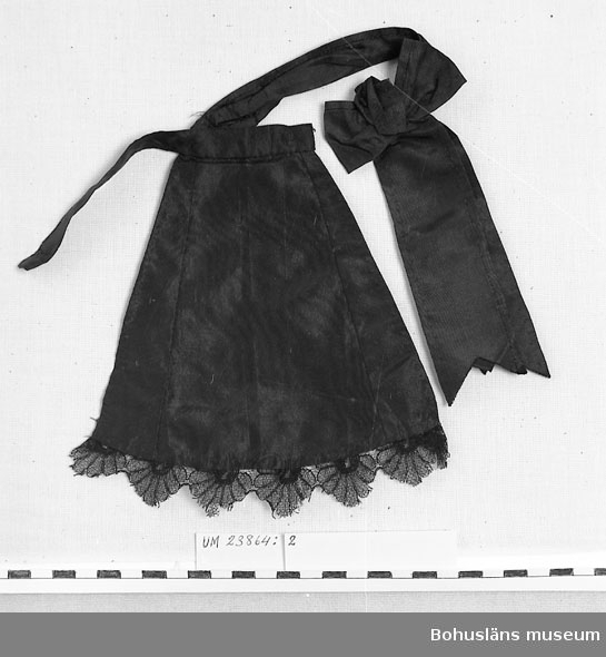 Svart tafttyg, bågformad nertill med spets av tyll. Avsmalnande upptill med insydda kilar i sidorna, samt midjeband med hyska och hake samt lös rosett med långa snibbar fastsättes med hake i sydd ögla.  UM023864:002 -UM023864:008 är de kläder som dockan UM023864:001 var klädd i vid insamlandet. Övriga kläder till dockan; se UM023865 - UM023901.  Personuppgifter; se UM023863.