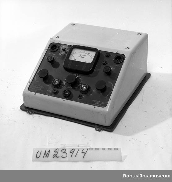 """ECT-apparat med instrumentpanel. Placerad i grå plåtlåda. Text: """"Mac Phail Strauss Plexacon. Universal electroplexy unit, serial No. For use on A.C. or D.C. 100-250 V or from 12 v battery. World patents pending""""."""