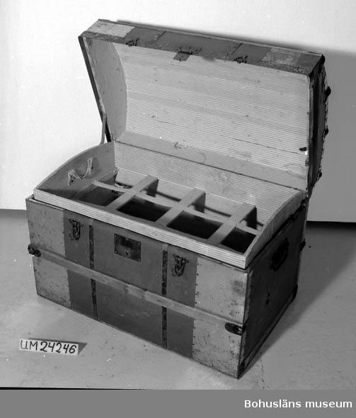 """Träkista klädd med tunn plåt. Lister av trä och svartmålad metall. Handtag på kortsidorna. Lås på ena långsidan (nyckel saknas). Stänganordning av metall. Klädd med vitt och rosa randigt papper på insidan. Välvt lock med bokstäverna """"GB"""" målade med svart. Givarens mor var brukare. Hon var född i Lidköping 15 augusti 1988. När hon var 21 år (1909) flyttade hon till Uddevalla. Då hade hon med sig kofferten. Hon var sömmerska bla på Schwartzman. Hon gifte sig Börjesson 1917 i Uddevalla."""