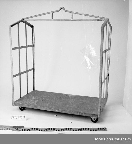 571 Användningstid 1954-65 CA 594 Landskap BOHUSLÄN  4-hjulsvagn. Gavlar av vinkeljärn med galler av lattjärn. Mellan gavlarna lyftanordning av rundjärn. Hjulen av plastliknande material, 2 vridbara. Specialbeställd. gjord för att passa transporter av kartonger som senare kom att ersättas av pallar ca 1954-65. Kompletterat med uppgift om funktionen antecknad på insamlingsblan- kett. 1999-06-30 VBT  Se även tidigare insamlade föremål UM018860 - UM018903.