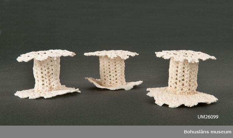 Virkade av vitt bomullsgarn med skaft, fot, ljuspipa, allt stärkt med sockerlösning. Något missfärgade. Personuppgifter se UM026024