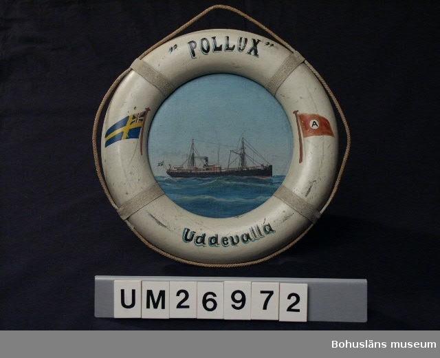 """Föremålet visas i basutställningen Uddevalla genom tiderna, Bohusläns museum, Uddevalla.  Tavla av en ångskonerten s/s Polux med ram i form av en livboj. Målningen är gjord på papp. Svart skrov med röda detaljer, två master samt skorsten som det kommer rök ur. Ovanför båten ljust vitaktigt blågrön himmel och under den böljande hav i grönt/blågrönt. Ramen av trä är vitmålad och på fyra ställen finns dekoration av påklistrat vitt bomullsband (nu gråaktigt pga smuts). Under bomullsbanden är en snodd trädd längs tavlans kant så att den ligger i lösa bågar runt hela ramen. Allt för att efterlikna en livboj. Upptill på ramen står: """"POLLUX"""", nertill Uddevalla, målat i svart och blågrönt. På högra sidan finns en målad bild av rederiets flagga, brunaktigt röd med en vit cirkel i mitten där det står A med svart. På vänstra sidan finns en bild av Sveriges handelsflagga, en svensk flagga som i övre inre fältet har unionsmärke använt 1844 - 1905 från unionen mellan Sverige och Norge. Datering till innan 1905 är gjord utifrån detta. Texten som anges under """"märkning"""" står på baksidan skrivet i skrivstil med bläck. På baksidan finns även en påklistrad pappersetikett med tryckt text: """"Gus. Karlson Marine Artist (Life=Buoys=Speciality) 75, Fords Park Rd., Canningtown E. and at 13, Derrick St., Rotherhithe S.E."""", med all sannolikhet tillverkarens namn.   1823 flyttade skotske affärsmannen William Thorburn till Uddevalla. Han lade grunden till ett familjeföretag som under ett och ett halvt sekel hade största betydelse för Uddevallas ekonomi. William Thorburn tog fasta på den engelska efterfrågan på havre till alla de hästar som drog Londons cabs och landsvägsdiligenser. Firman Thorburn och söner köpte upp havre från bönderna i Bohuslän, Västergötland och Dalsland. Jordbruket inriktades alltmer på havreodling.   1867 startade William Thorburn ångbåtsförbildelse Uddevalla - London under namnet Ångbåtsaktiebolaget Avena. Avena betyder just havre. De ingående fartygen var s/s Avena,s/s  Si"""