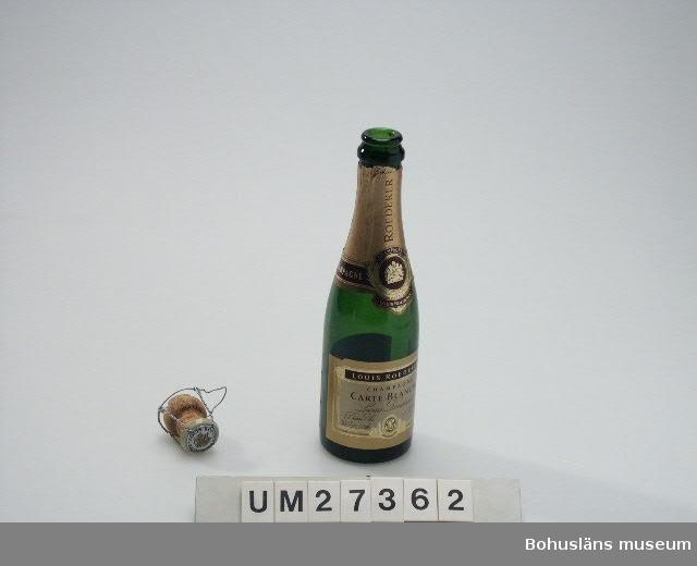 """Champagneflaska (:1) i grönt glas med pappersetikett om hals och buk, 375 ml. Kork (:2) med text """"Louis Roederer"""" och tillslutning av virad metalltråd.  Se även Bilagepärmen UM27361 för exempel på varningsartikel som publicerades i pressen i januari 2000 med anledning av exploderande cider- och champagneflaskor.  För information om Millennieinsamlingen, se UM27360."""