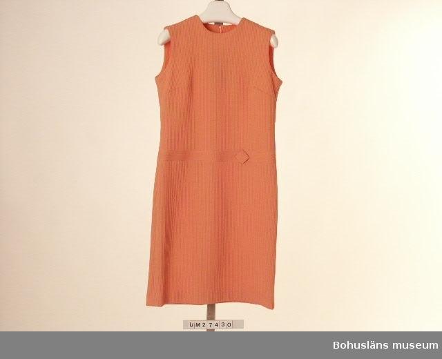 """Föremålet visas i basutställningen Uddevalla genom tiderna, Bohusläns museum, Uddevalla.  Laxrosa klänning av tyg vävt i reliefrandig effekt, liknande tyget i UM027429. Tyget skuret så att randningen är vertikal. Rak, enkel, något utsvängd modell med rund halsringning. Höften markeras av ett 3,5 cm brett infällt stycke där reliefrandningen ligger horisontellt.  På denna sitter till vänster ett fyrkantigt vikt tygstycke på högkant som dekor. Bystveck. Bakstycke i två våder med en 53 cm lång dragkedja i mitten. Ofodrad.  Etiketter i halsringningen med med texten: """"Magna 42"""" I dragkedjan vidhängande pappersetiketter i silkessnöre med texten: """"Magna / 'Magnalene' 100% crimped polyester"""", andra sidan: """"Varudekl. Modell  F  24 Kval 152 Färg  5 Storlek  42 Pris"""" Vid platsen för pris har Prylmarknaden fäst en klisterlapp med texten """"Kr 45.-"""" Obegagnad vid förvärvet.  För ytterligare uppgifter om förvärvet och övrigt material rörande Magnas produktion i museets samlingar, bl.a.  dokumentation 1998, se UM027416."""