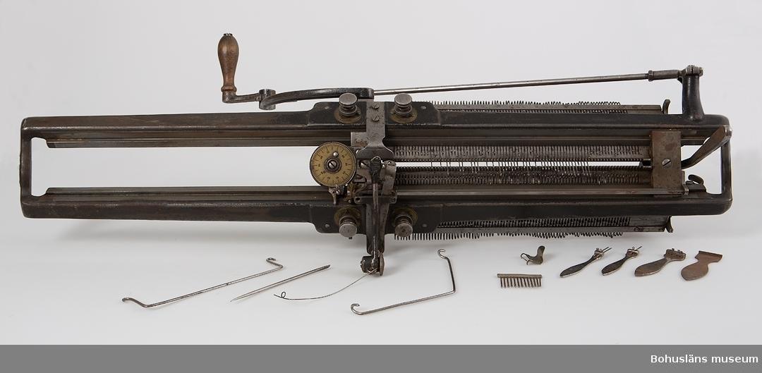 """Stickmaskin, flatstickningsmaskin, bestående av en stor maskindel, ett stativ med separat anskruvningsdel och ett svänghjul. Stora maskinen inlindad i kraftig svart ylletygbit. I en trälåda med pappersetikett """"Nissens Manufacturing"""" förvaras flera smådelar till maskinen, bl a sex metalltyngder placerade i två krokar, åtta träspolar, två metallband med krokar. Samtliga delar är märkta: UM27948. Ytterligare: Låda betsad röd/brunt med lock som sitter fast med två gångjärn. Lådan stängs med två små krokar. På locket finns ett handtag av metall. På insidan locket finns en garantisedel utfärdad den 20 september 1920. Där står bl a att maskinen är avsynad av G.O och packad av H-d. Tillverkningsnummer: 6974.  Lådan innehåller 3 st tyngder, mejsel, långkrok, spännfjäder, kort krok, arbetskrok, 2 st spolar, 1 st lös nålbädd, 2 st vikta ark innehållandes nålar, en tändsticksask med nålar, 2 st vaxbitar inslagna i papper, 1 st korg, 1 st ledarskiva med nålbädd, ett tomt kuvert samt  häftet """"Bruksanvisning för stickning på Stickmaskinen """"FAVORIT"""" från Aktiebolaget Lindéns Hemmaskiner Nässjö Rikstelefon 162"""". Det fattas vissa delar jmrf med sid 77 - 78 i bruksanvisningen.   Det finns ett """"skruvjärn"""" som maskinen sätts fast med i bordsskivan. Det är inte en originaldel.  Till materialet hör två handskrivna mönsterböcker, en äldre liten utan pärmar och en yngre med svarta vaxdukspärmar. I den äldre finns mönster för t ex Damstrumpor, Damask till en 9 åring, Manströja och i den yngre mönster till  t ex Egons strumpor, Nisses tröja, 9 års vantar, 2 års barnunderlif, Herberts tröja, Damunderlif samt några barnteckningar, bl. a. en """"huvudfoting""""."""